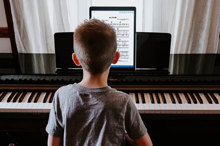 Young boy playing piano with Musicnotes app on iPad